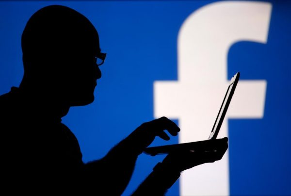 A man is silhouetted against a video screen with an Facebook logo as he poses with an Dell laptop in this photo illustration taken in the central Bosnian town of Zenica, August 14, 2013. REUTERS/Dado Ruvic (BOSNIA AND HERZEGOVINA - Tags: BUSINESS TELECOMS) - RTX12L6Y